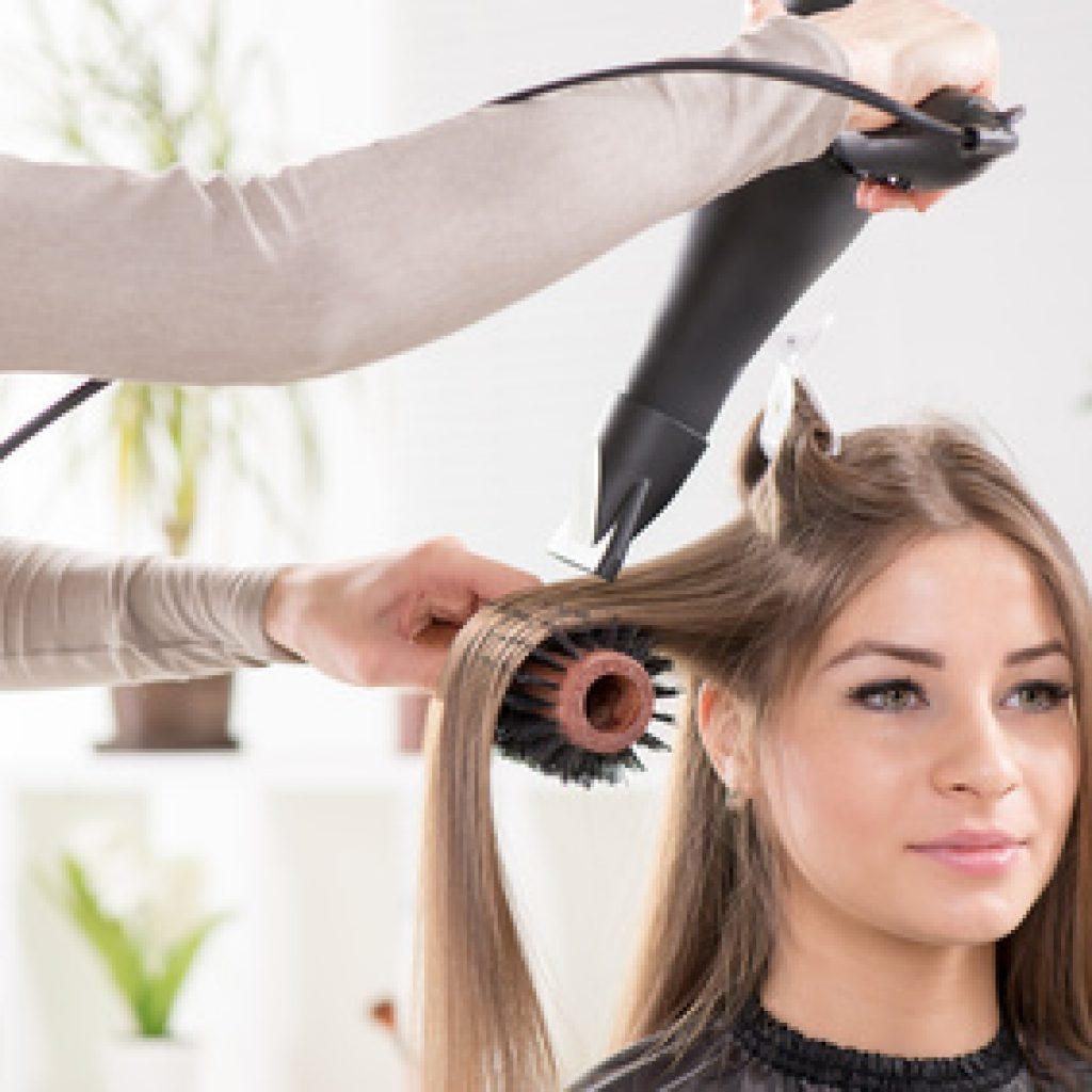 Hairdresser drying long brown hair with hair dryer and round brush.