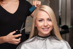 Happy young woman getting new haircut by hairdresser at parlor. hairdresser cutting client's hair in beauty salon